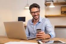 Un homme avec un téléphone et un ordinateur