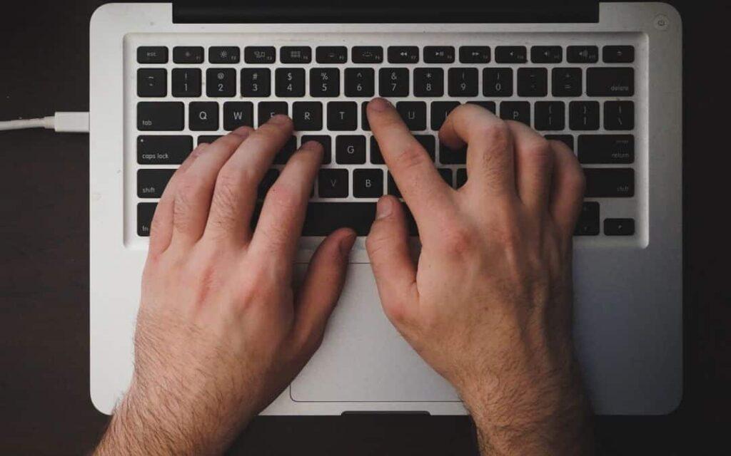 Mains d'homme tapant sur un clavier ordi